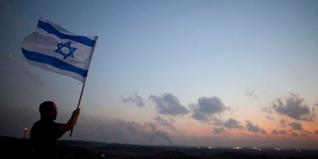 SDEROT, ISRAEL - JULY 20:  (ISRAEL OUT) A man stands with an Israeli flag on a hill overlooking the Gaza Strip on July 20, 2014 near Sderot, Israel. Thirteen Israeli soldiers were killed Sunday in battle in the Gaza Strip, bringing the number of Israeli fatalities over the course of the operation to 20.  At least 130 Palestinians have been killed since Israel began its ground incursion last week.  (Photo by Lior Mizrahi/Getty Images)