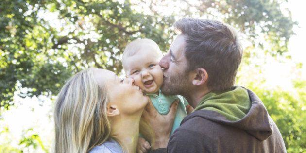 Caucasian couple kissing baby in backyard