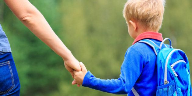 Mother holding hand of little son with backpack outdoors, back to