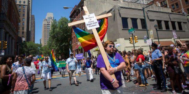 PHILADELPHIA, PA - JUNE 12: Austin Ellis, a member of Metropolitan Community Church, carries a cross...