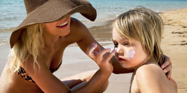 Mother putting sunscreen on her son at the