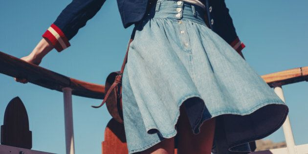A young woman's skirt is blowing in the wind as she is standing on the deck of a boat cruising down the