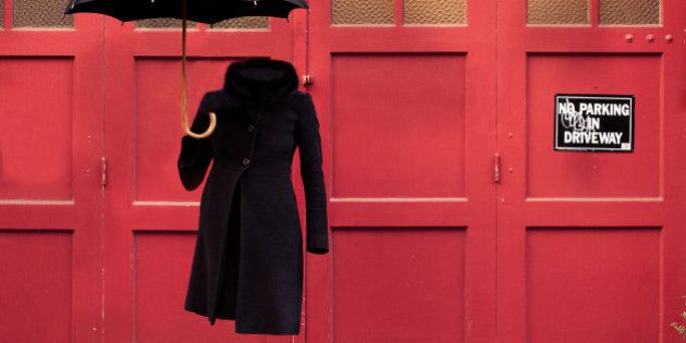 'Invisible' woman in winter coat with high heels and umbrella against red garage door.
