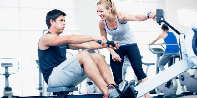 Personal trainer with man on rowing machine in