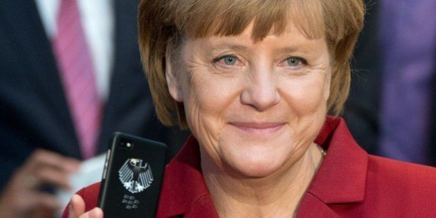 German Chancellor Angela Merkel holds a tapping proof BlackBerry mobile device at the stand of Secusmart...