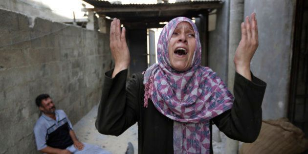As her brother-in-law Mazen Keferna, background left, weeps, Palestinian Manal Keferna, 30, right, cries...
