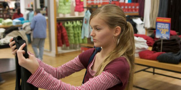 Girl holds up a shirt in a clothing store deciding whether to buy