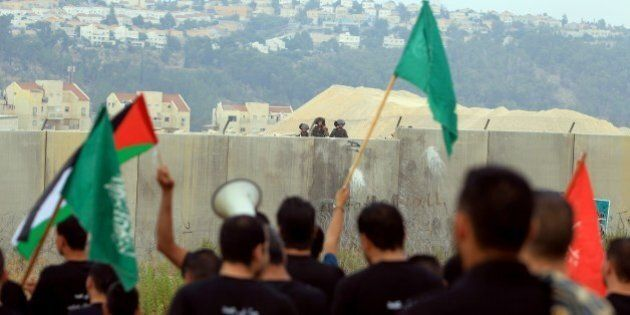 Palestinian protesters, holding national flags and the flag of the Islamist Hamas movement (green), take...