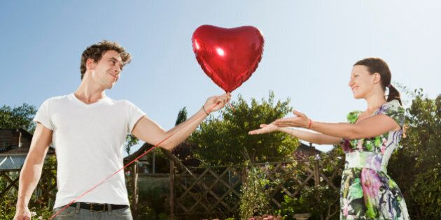 Man gives heartshaped balloon to woman.