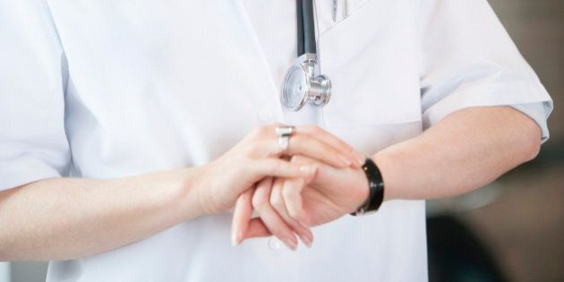 Female doctor checking the time
