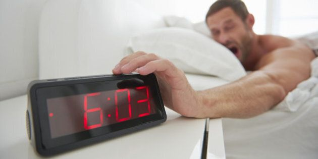 Man reaching for alarm clock from