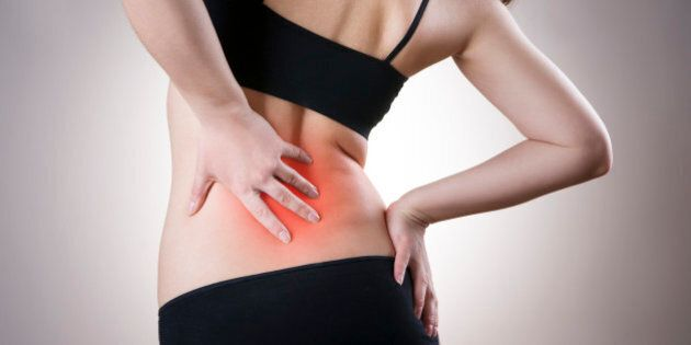 Pain in back of women on gray background. Caring for the female body. Red