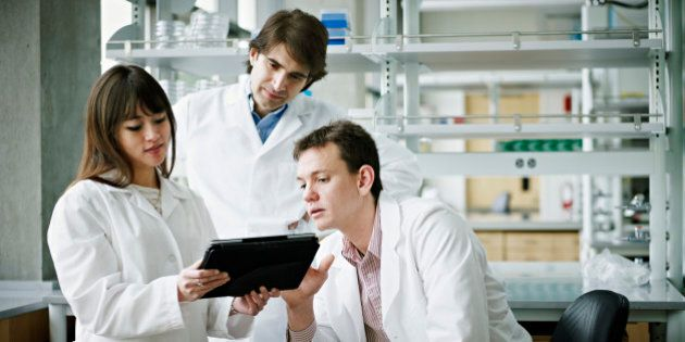 Three scientists in research laboratory discussing project on digital
