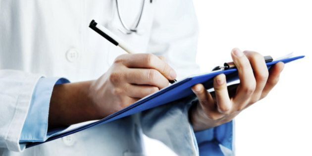 Unrecognizable doctor writing a medical chart. Isolated on white