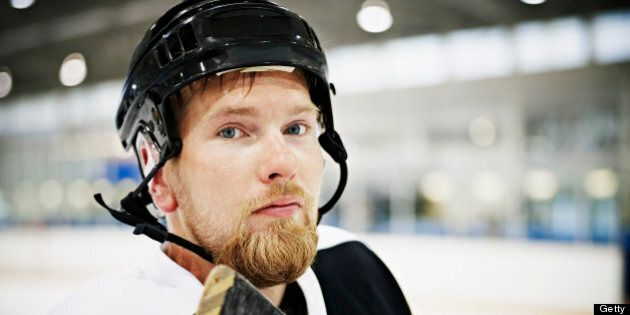 Portrait of ice hockey player standing on ice in hockey arena wearing helmet