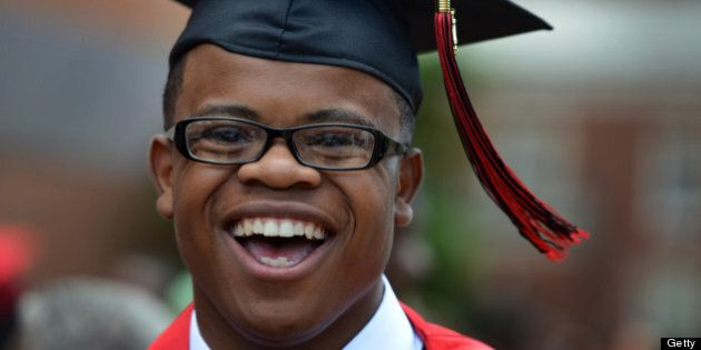 WASHINGTON, DC - JUNE 14: Johnathon Carrington, valedictorian at Dunbar High School, laughs with family and friends after his school's graduation ceremony at Howard University on Friday, June 14, 2013, in Washington, DC.  Carrington, who grew up in Tyler House public-housing apartments and is graduating from one of DC's low-performing high schools, plans to attend Georgetown University, where academic expectations are high.      (Photo by Jahi Chikwendiu/The Washington Post via Getty Images)