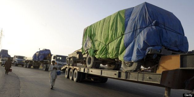 Pakistani vendors walk past trailers carrying NATO military equipment bound for Karachi, following their...