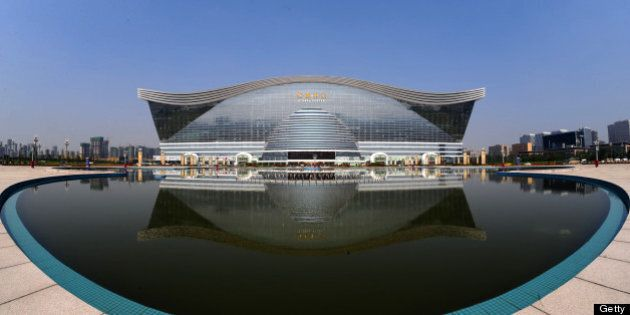 The 'New Century Global Centre' building is seen behind an artificial lake in Chengdu, in southwest China's Sichuan province on June 6, 2013. The center, claimed by Chinese officials as 'the world's largest standalone structure', is going to be opened to the public on June 28. The 100m high 'New Century Global Centre' is a symbol of the spread of China's boom: 500m long and 400m wide, with 1.7 million square metres of floor space - big enough to hold 20 Sydney Opera Houses, according to local authorities.  CHINA OUT     AFP PHOTO        (Photo credit should read STR/AFP/Getty Images)