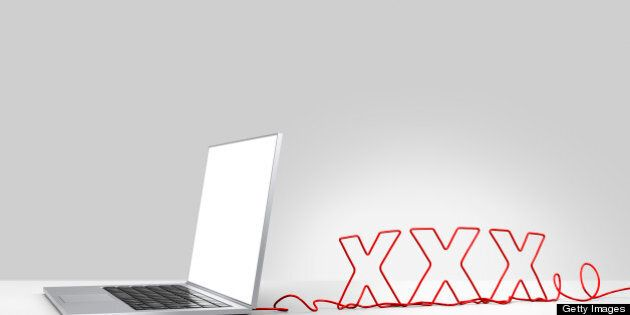 Laptop computer with a red ethernet cable forming 'XXX', coming out of the back on a plain