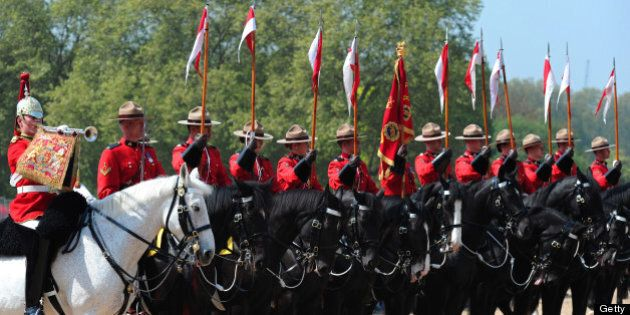 Members of the Royal Canadian Mounted Police (R) parade with British Guards (Far L) on Horse Guards Parade...