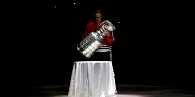 Chicago Blackhawks defenseman Duncan Keith carries out the Stanley Cup during a banner raising ceremony...