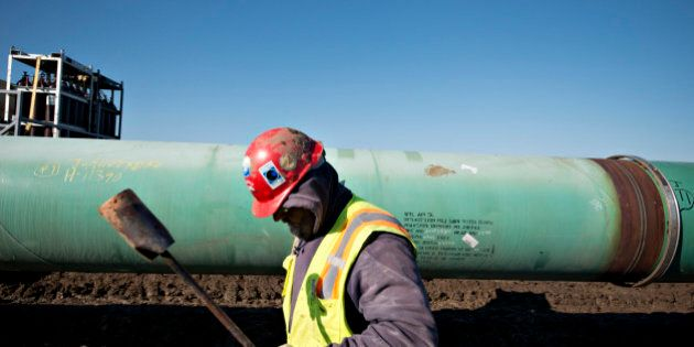 A worker carries a torch after heating a pipe joint during construction of the Gulf Coast Project pipeline...