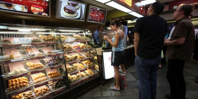 Costumers line up at the Tim Hortons coffee shop inside New York's Penn Station, Monday, July 13, 2009. Canadian doughnut and coffee chain Tim Hortons Inc. said it is opening 12 new locations in New York City, with three more planned for August.  (AP Photo/Mary Altaffer)