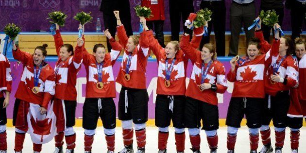 Members of Canada's women hockey team celebrate after they received their gold medals for a 3-2 overtime...