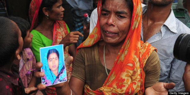 A Bangladeshi woman shows a portrait of her missing daughter in-law, believed trapped in the rubble following...