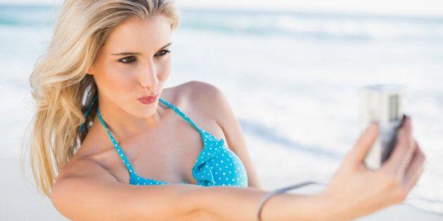 Happy sexy blonde in bikini taking a self picture on a beautiful sunny beach
