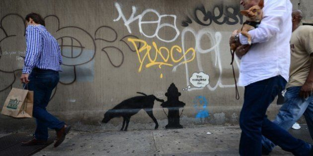 People walk by a street art graffiti by elusive British artist Banksy, as part of his month-long Better Out Than In exhibit, in New York, October 3, 2013. Banksy will be attempting to host an entire show on the streets of New York during a month residency. AFP PHOTO/Emmanuel Dunand (Photo credit should read EMMANUEL DUNAND/AFP/Getty Images)