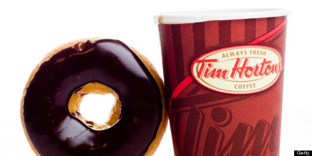 A cup of Tim Hortons Inc. coffee and doughnut are arranged for a photograph in Toronto, Ontario, Canada,...