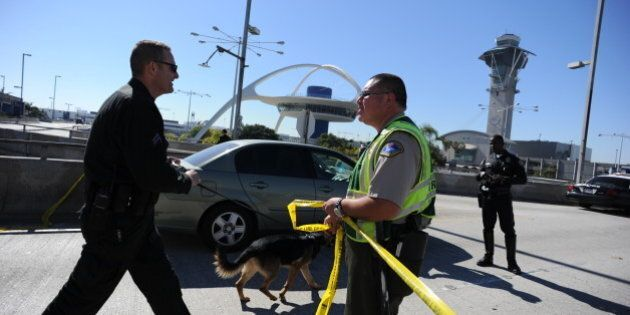 A K-9 officer (L) crosses a crime tape line on November 1, 2013 after a gunman reportedly opened fire...