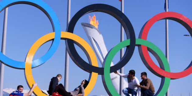 People pose in the Olympic Rings in the Olympic park during the Sochi Winter Olympics on February 15,...