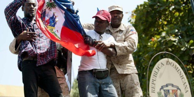 Haitian police remove protestors who tried to place the Haitian flag on the mast of the Consulate General...