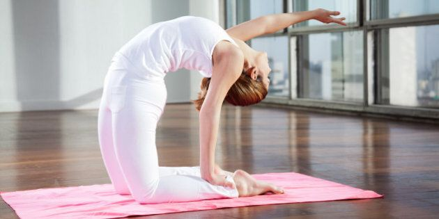Full length of a young woman practicing yoga in Camel position on mat