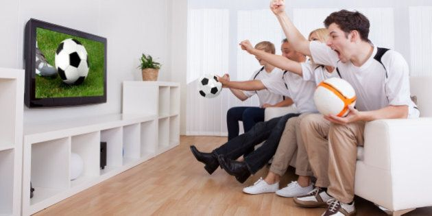 Jubilant family watching television as they cheer on their home side in a sporting
