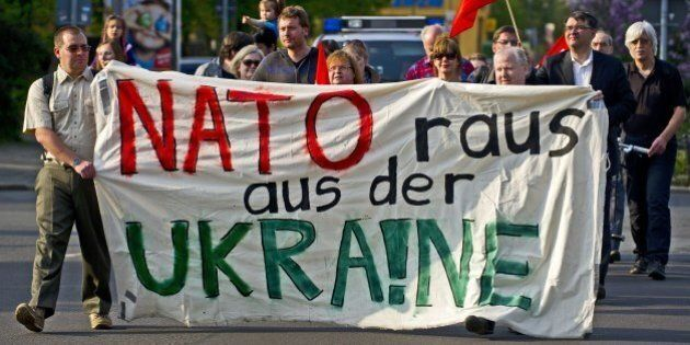 Protestors hold a banner reading 'Nato get out of the Ukraine' in front of the Westin Hotel where the...