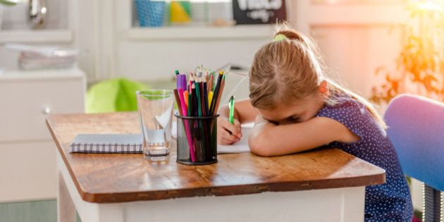 Girl in blue shirt having problem with concentration to finish home