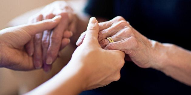 Cropped shot of a person holding an elderly woman's