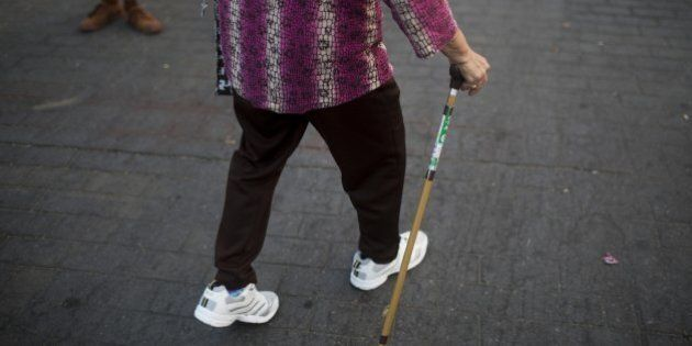 A woman uses a walking cane as she walks at Lumphini Park in Bangkok, Thailand, on Sunday, March 15,...