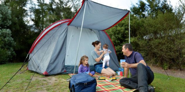 Young family, father and mother with two children camping in a tent
