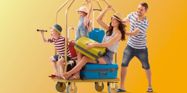 a young family climb aboard a luggage trolley and dad pushes them off to their holiday destination ....