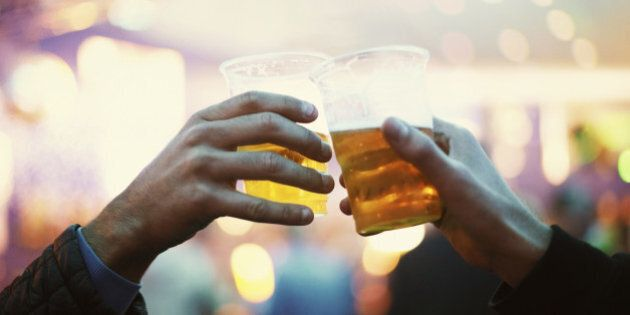 Two friends toasting to the good times with plastic cups of beer - Music