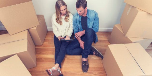 Young couple sitting in new house with packing boxes. They look like they have just moved in and they...