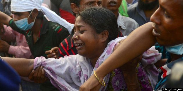 Bangladeshi relatives react after looking at the coffin of a victim following the collapse of an eight-storey...
