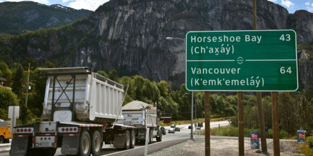 A bilingual roadside mileage sign is shown along the Sea to Sky Highway in Squamish, British Columbia,...