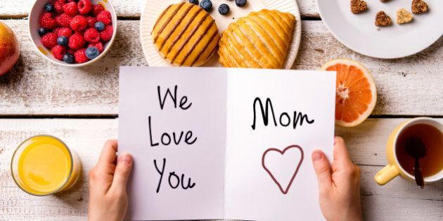 Mothers day composition. Hands of unrecognizable woman holding greeting card with We love you, Mom, text. Breakfast meal. Studio shot on wooden background.