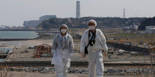 In this photo taken Thursday, April 17, 2014, Kazuhiro Onuki, right, and his wife, Michiko, wearing white...