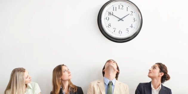 Four businesspeople sitting on bench and looking up at clock. Horizontally framed